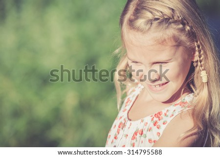 portrait of a beautiful young little girl  in park at the day time