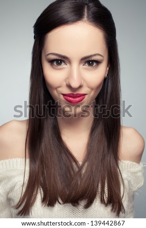 Portrait of a beautiful young long-haired brunette smiling and posing over light-gray background. Healthy skin. Studio shot