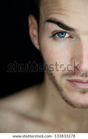 Portrait of a beautiful young man half face - stock photo