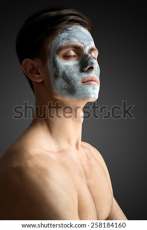 Portrait of a beautiful young man with a facial clay mask, face and body skin care treatment. - stock photo