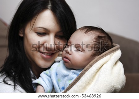Portrait of a beautiful young mother holding her beautiful baby boy. - stock photo