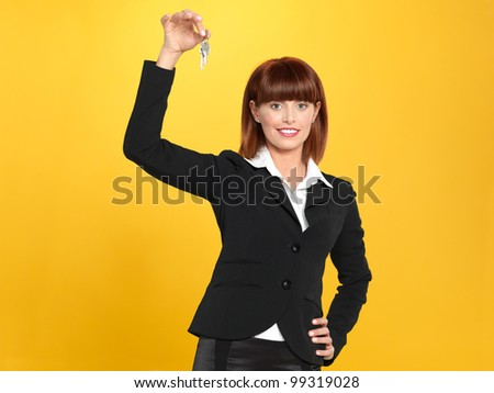 portrait of a beautiful, young realtor businesswoman, holding a house key in her hand, on yellow background - stock photo