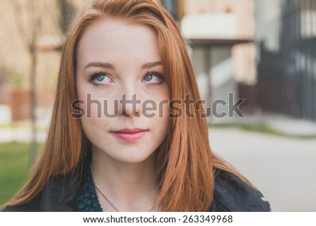 Portrait of a beautiful young redhead girl posing in the city streets - stock photo