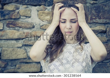 portrait of a beautiful young sad girl standing near the wall outdoors at the day time - stock photo