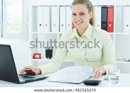 Portrait of a beautiful young secretary working on laptop sitting at office. Business, exchange market, job offer, analytics research, excellent education, certified public accountant concept
