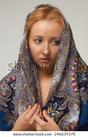 Portrait of a beautiful young sexy woman with long blonde hair with natural natural makeup wearing a beige T-shirt tight head is covered with a colored shawl