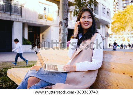 Portrait of a beautiful young smiling asian woman holding on her portable laptop computer while sitting on a wooden bench and talking on the smart-phone - stock photo