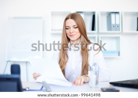 Portrait of a beautiful young smiling business woman doing some paperwork in bright office - stock photo