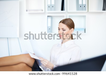 Portrait of a beautiful young smiling business woman doing some paperwork with legs on desk at office in bright office - stock photo