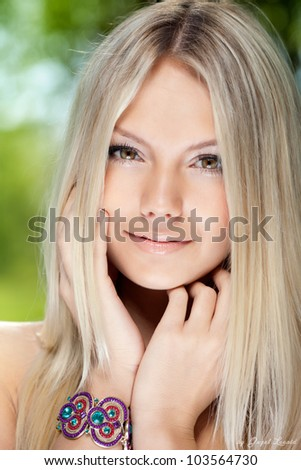Portrait of a beautiful young smiling woman with blonde hair close-up - stock photo