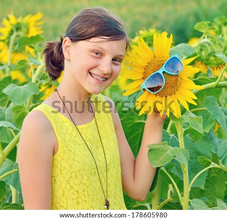 Portrait of a beautiful young Teenage on sunflower field - stock photo