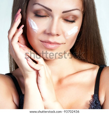 Portrait of a beautiful young woman applying face cream on her cheek