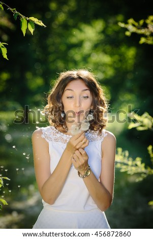 Portrait of a beautiful young woman blowing dandelion flower