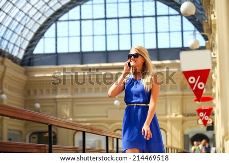 Portrait of a beautiful young woman calling by phone in shop - stock photo