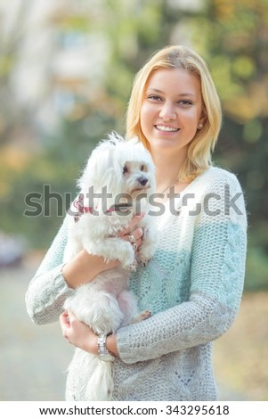 Portrait of a beautiful young woman carrying her cute little Maltese dog - stock photo