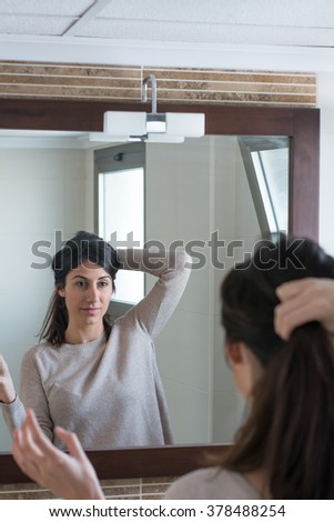 Portrait of a beautiful young woman combing hair and put on make up in front of her bathroom mirror