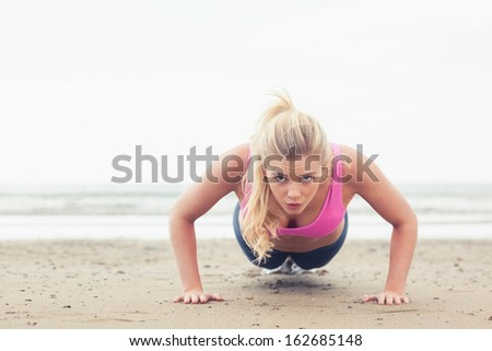 Portrait of a beautiful young woman doing push ups on the beach - stock photo