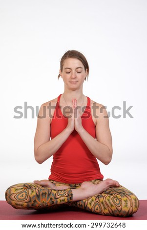 Portrait of a beautiful young woman doing yoga on isolated white background at photo studio. - stock photo