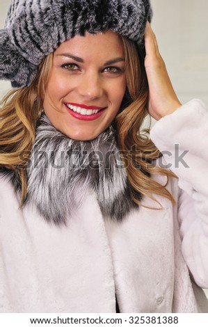 portrait of a beautiful young woman dressed in white fur coat and grey hat - stock photo