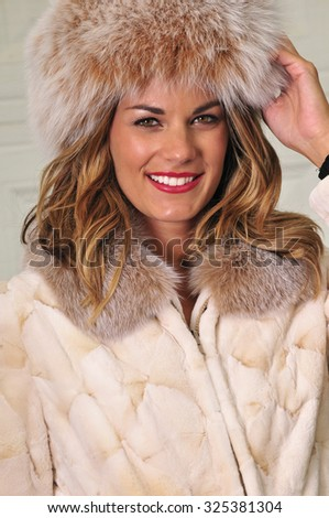 portrait of a beautiful young woman dressed in winter fur coat and hat - stock photo