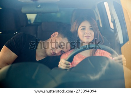 Portrait of a beautiful young woman driving a car while her boyfriend falls asleep on her shoulder - stock photo