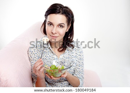 Portrait of a beautiful young woman eating vegetable salad. - stock photo