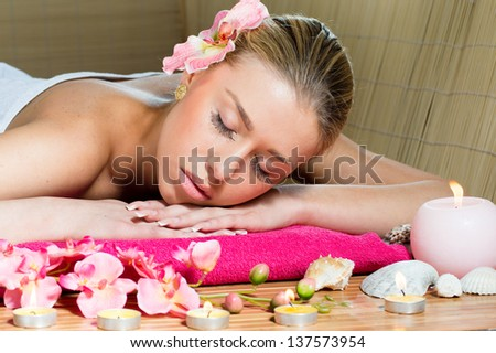 Portrait of a beautiful young woman face with perfect skin in relaxation during massage treatment