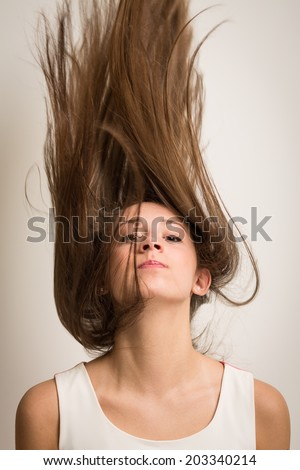 Portrait of a beautiful young woman flipping her hair up in the air making it look like it's standing up. Isolated against a light grey background