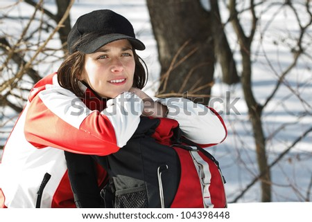 Portrait of a beautiful young woman going on trip with sporty clothes, cap, rucksack, sitting next to her rucksack, smiling - stock photo