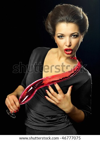 Portrait of a beautiful young woman holding a glass of red wine with splash