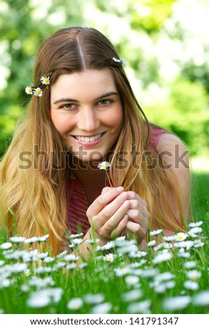 Portrait of a beautiful young woman holding flower in the park