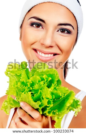 Portrait of a beautiful young woman holding fresh green lettuce. Isolated over white background. - stock photo