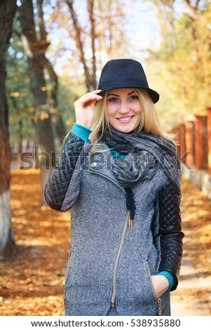 Portrait of a beautiful young woman in a autumn park.