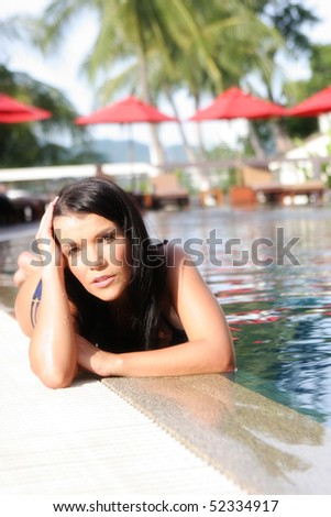 Portrait of a beautiful young woman in a bikini by the swimming pool.