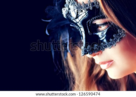 Portrait of a beautiful young woman in a carnival mask. Over black background. - stock photo