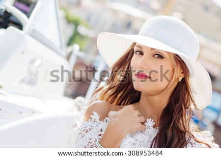 Portrait of a beautiful young woman in a hat on the quay - stock photo