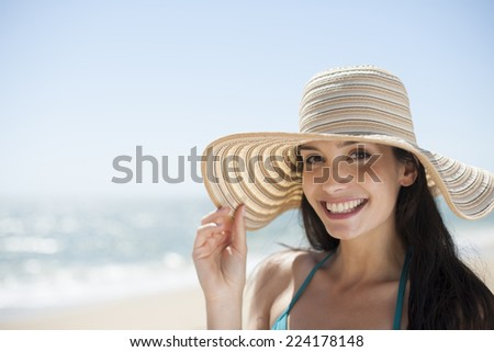 portrait of a beautiful young woman in a swimsuit on the beach protecting herself from the sun with a big hat - stock photo