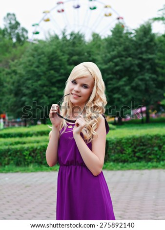 Portrait of a beautiful young woman in a violet dress in park  - stock photo