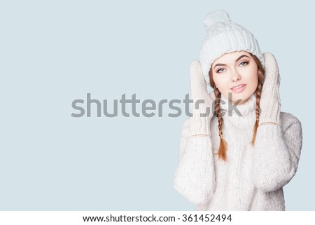 Portrait of a beautiful young woman in a warm cozy knitted dress, she is dressed in a light head cap and mittens. Elegant young woman in dress, NEW YEAR