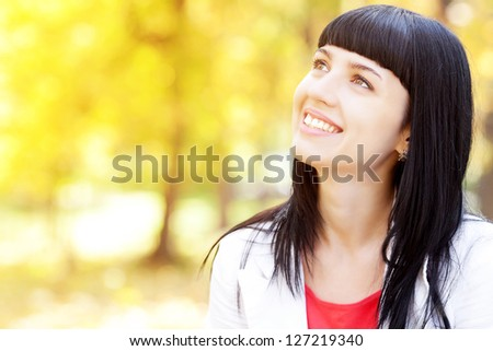 portrait of a beautiful young woman in autumn forest - stock photo