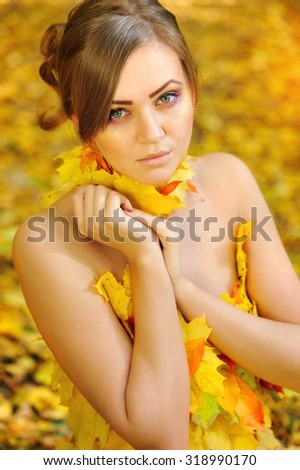 Portrait of a beautiful young woman in autumn leaves - stock photo