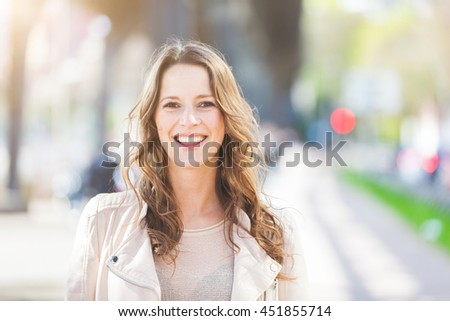 Portrait of a beautiful young woman in Hamburg. She is caucasian, on her early twenties, brunette with long hair. Looking at camera and smiling. Smart casual clothes, blurred urban background