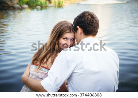 Portrait of a beautiful young woman in love on nature woman hugging man - stock photo
