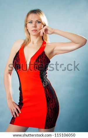 Portrait of a beautiful young woman in red dress - stock photo