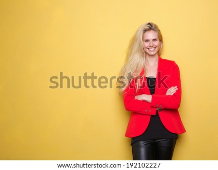 Portrait of a beautiful young woman in red jacket smiling on yellow background