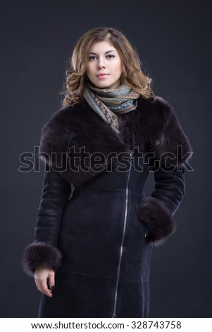 Portrait of a beautiful young woman in sheepskin coat with fur collar