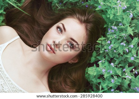 Portrait of a beautiful young woman in summer garden. Girl on nature. Spring flowers. Fashion beauty - stock photo
