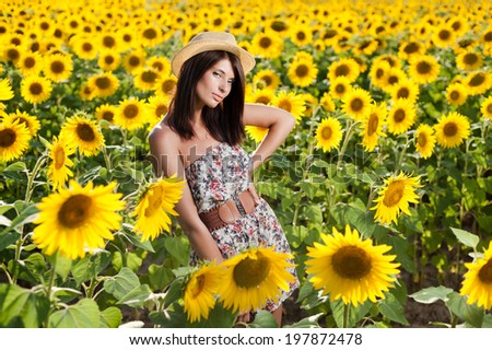 Portrait of a beautiful young woman in sunflower field. - stock photo