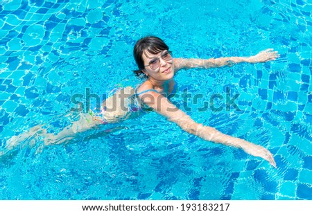Portrait of a beautiful young woman in sunglasses floating in the pool. Concept photo healthy lifestyle