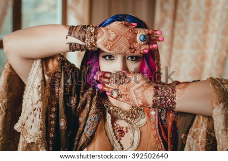 portrait of a beautiful young woman in traditional Indian ethnic dress and painted ational patterns on the hands, mehendi - stock photo